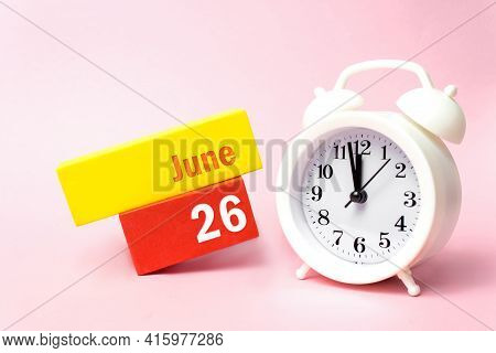 June 26th. Day 26 Of Month, Calendar Date. White Alarm Clock On Pastel Pink Background. Summer Month