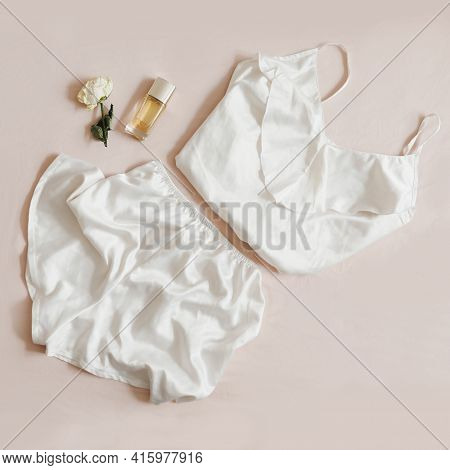 Women Silk Lingerie, Perfume And A Rose On Beige Background, Flatlay, Top View. Female Elegant Lace