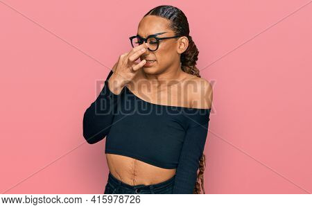 Hispanic transgender female wearing make up and long hair wearing women clothes smelling something stinky and disgusting, intolerable smell, holding breath with fingers on nose. bad smell