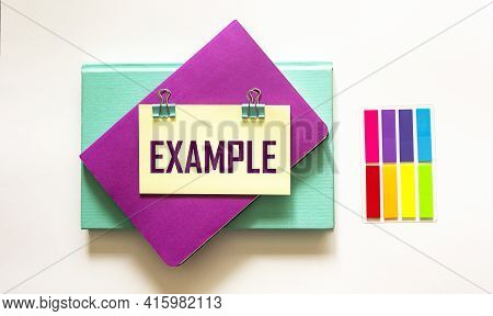 Example, The Word Is Written On A Sticker And A White Background. The Sticker Lies On The Example On
