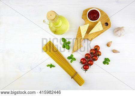 Ingredients For Homemade Pasta: Linguini, Tomato, Sauce, Cheese On A White Wooden Background. Top Vi