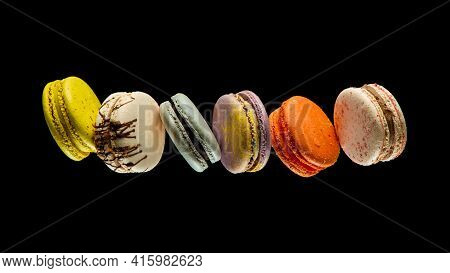 Set Of Flying Colorful Macaroons Isolated On Black Background Macaron Or Macaroon Cakes Hang In The