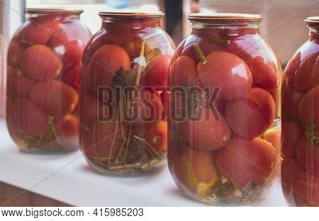 Home Preservation: Large Glass Jars With Red Ripe Pickled Tomatoes, Closed With Metal Lids, Stand On