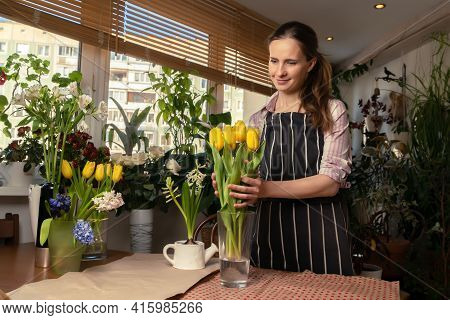 Beautiful Woman Florist Making A Bouquet Of Yellow Tulip Flowers Indoors At Flower Shop Salon