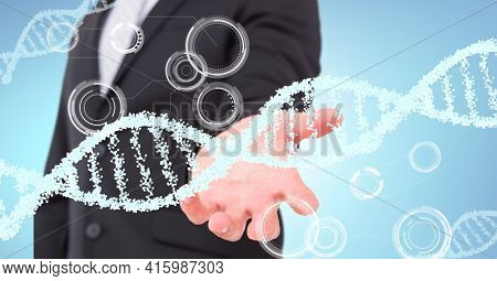Dna structure and round scanners over mid section of business man with cupped hand. global business and medical research technology concept