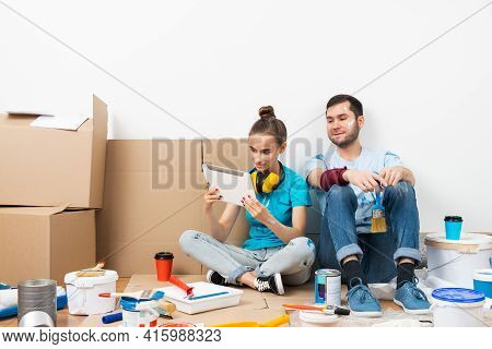 Happy Couple Sitting On Floor And Looking At Tablet Computer Screen. Home Remodeling And House Inter
