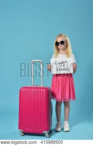 Serious Girl Child Holding A Signboard With Request I Want To Travel.