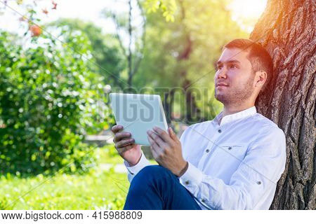 Dreamy Man Using Tablet Computer Under Tree In Park On Sunny Day. Handsome Businessman Looking Over