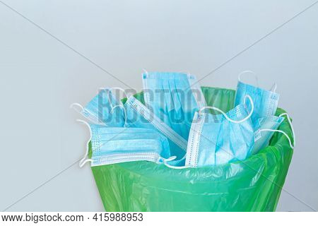 Used Infectious Mask Thrown In Trash Bin. Discarded Disposable Surgical Masks. Medical Waste Concept