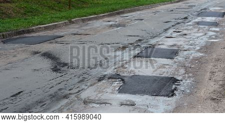 Asphalt Road Repair Of Poor Quality. Pothole Asphalt Road Repairs. A Newly Patched Roadway In A Bad