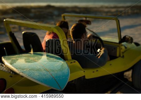 Caucasian couple sitting in beach buggy by the sea talking. beach break on summer holiday road trip.