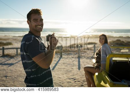 Caucasian couple on beach, man holding camera smiling, woman sitting on beach buggy playing guitar. beach break on summer holiday road trip.