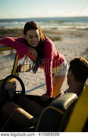 Happy caucasian couple on beach woman leaning on beach buggy man sitting behind steering wheel. beach break on summer holiday road trip.