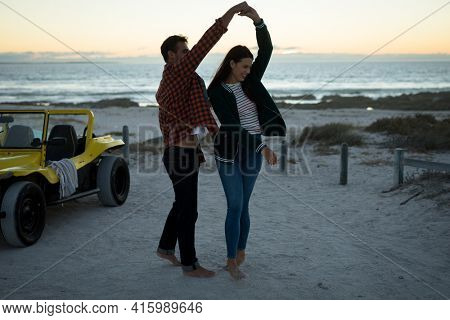 Happy caucasian couple next to beach buggy by the sea dancing. beach break on summer holiday road trip