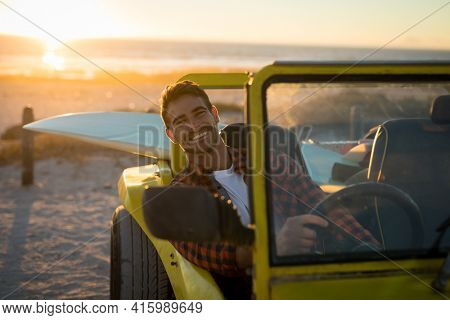 Happy caucasian man sitting in beach buggy by the sea during sunset smiling. beach break on summer holiday road trip.