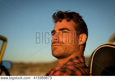 Portrait of caucasian man watching sunset in beach baggy. beach break on summer holiday road trip.