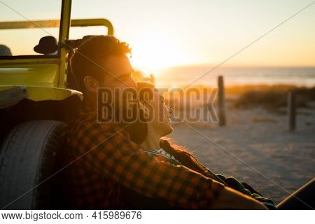 Happy caucasian couple leaning against beach buggy by the sea relaxing during sunset. beach break on summer holiday road trip.