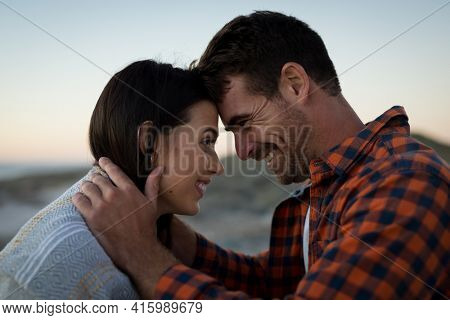 Happy caucasian couple on beach at the sea touching foreheads. love, romance and beach break summer holiday.