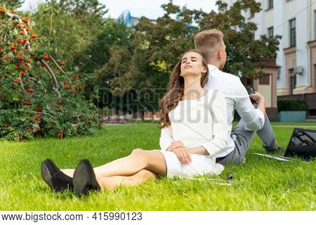 Business Persons In The Park Sit On The Grass In The Park