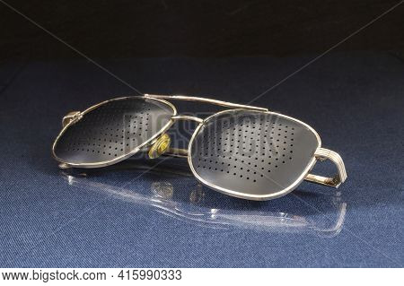 Glasses With Holes For The Treatment Of Myopia On The Table With A Reflection. Personal Items On A B