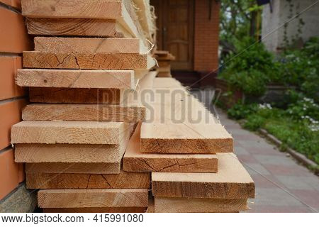 Wooden Building Materials: A Stack Of Wood Boards, Planks And Sawn Timber Stored Near The House Duri