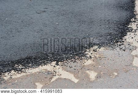 A Close-up Of A Pothole Repair On The Road, Repaired Patched Asphalt Driveway. Old And New Asphalt O
