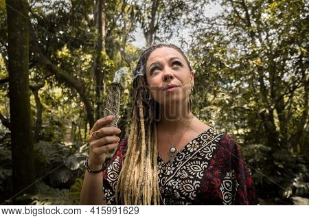 Caucasian Woman With Dreadlocks Holding Incense In Her Right Hand And Looking At The Sky. She Has A