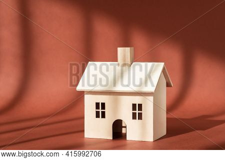 Wooden House Building Miniature Model With Shadow On Brown Background. Home, Sweet Home. Buying New