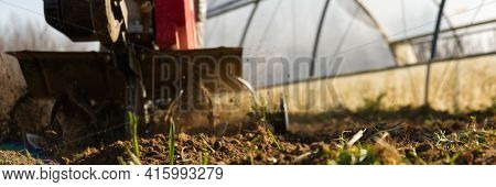 Narrow Perspective From The Ground Of A Cutter Ploughing The Ground. High Quality Photo
