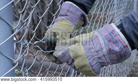 Installing And Fastening A Galvanized Mesh To A Metal Post When Creating A Fence On A Farm Or Backya