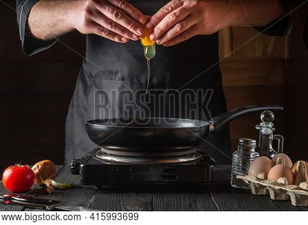 The Yolk Falls Into A Frying Pan From A Cracked Raw Egg, Split By The Hands Of The Cook. Working Env