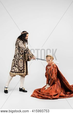 Full Length Of Cruel Hispanic King In Medieval Clothing Holding Sword Near Scared Blonde Queen In Cr