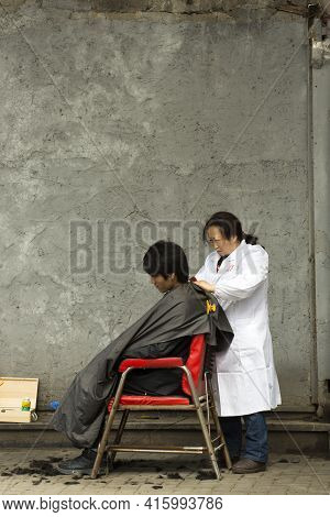 Shanghai, China, April 3: Unidentified Woman Hairdresser Working With A Customer Man In The Streets