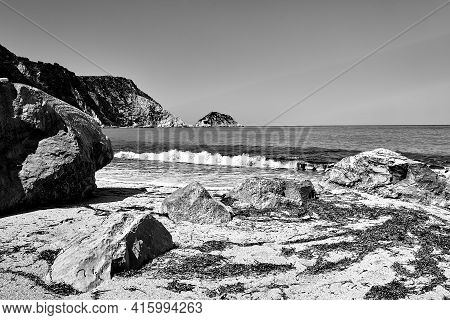 Boulders On The Sandy Beach At Petani Bay On The Island Of Cephalonia In Greece, Monochrome