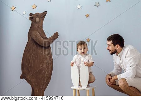 Dad And Son Play Together In A Children's Room. The Child Sits On A Children's Chair And Looks At Th