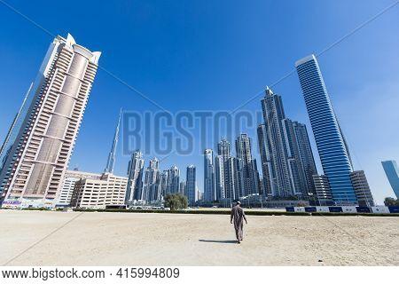 Dubai, United Arab Emirates - January 8: Arab Man Walking With Dubai Skyline With Residential Skyscr