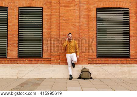 A Young Hispanic Man Talking On His Smart Phone, On A Street Outdoors. Lifestyle Concept. Yellow And