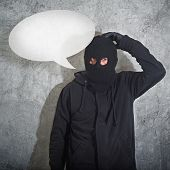Confused burglar with speech balloonconcept thief with balaclava caught confused and without idea in front of the grunge concrete wall. poster