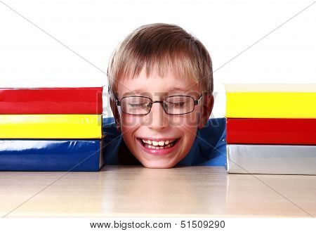 Blond cheerful schoolboy sitting at a table with a stack of colorful books laughing (isolated on whi