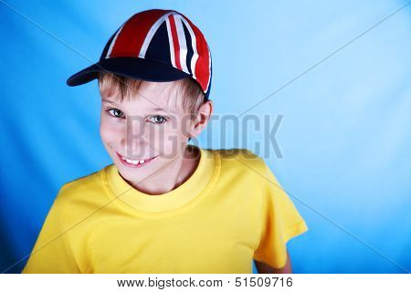 Cute blond boy in a yellow t-shirt wearing a baseball cap with a British national flag smiling
