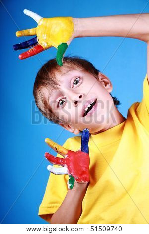 Beautiful cheerful blond boy in a yellow t-shirt showing multicolored painted hands and smiling happ