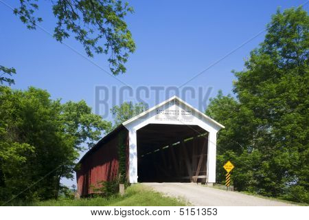 The McAllister Covered Bridge crosses Little Raccoon Creek on County Road East 400 South in Parke County. This single span Burr Arch Truss structure has a length of 126 feet or 144 feet including the 9-foot overhang at each end. Built in 1914 by Joseph A. poster