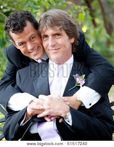Portrait of a handsome gay couple in their wedding tuxedos.