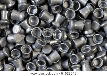 Pile of lead air-gun pellets close-up background texture poster