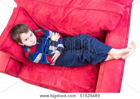 Eight years old boy expression mischievousness with arms closed on the couch by looking up in to your eyes isolated on white poster
