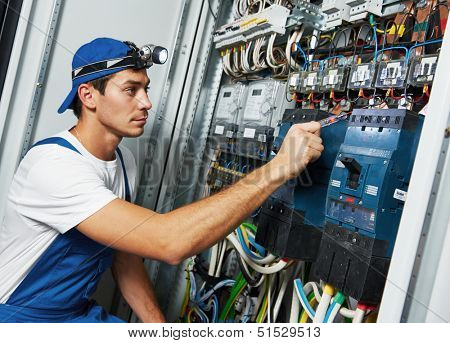 Young adult electrician builder engineer screwing equipment in fuse box poster