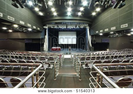 Rows of chairs and stage with desk in modern hall for business meetings.