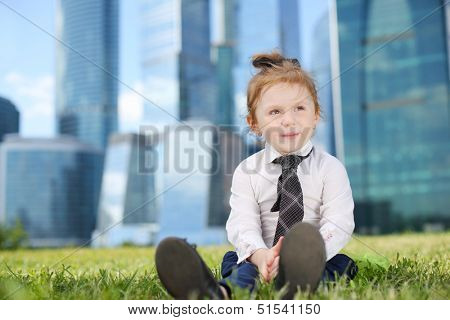 Little cute girl in white shirt and tie sits on grass near skys?rapers at sunny day.
