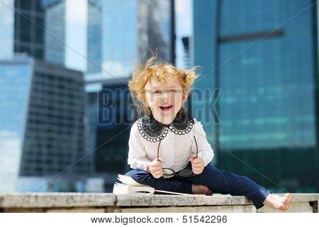 Little cute girl with book and glasses sits on border and laughs near skys?raper at sunny day.