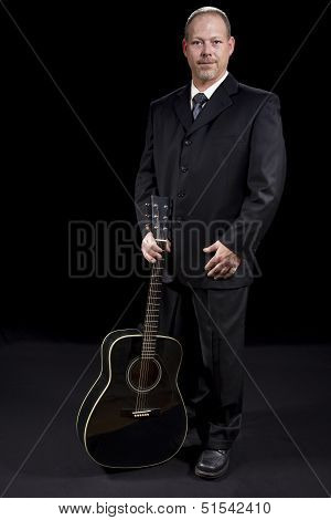 Successful Business Man In Suit Standing With Guitar On Black Background